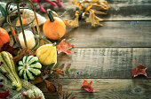 Fall Arrangement of Pumpkins, Gourds and Leaves on a Wood Background
