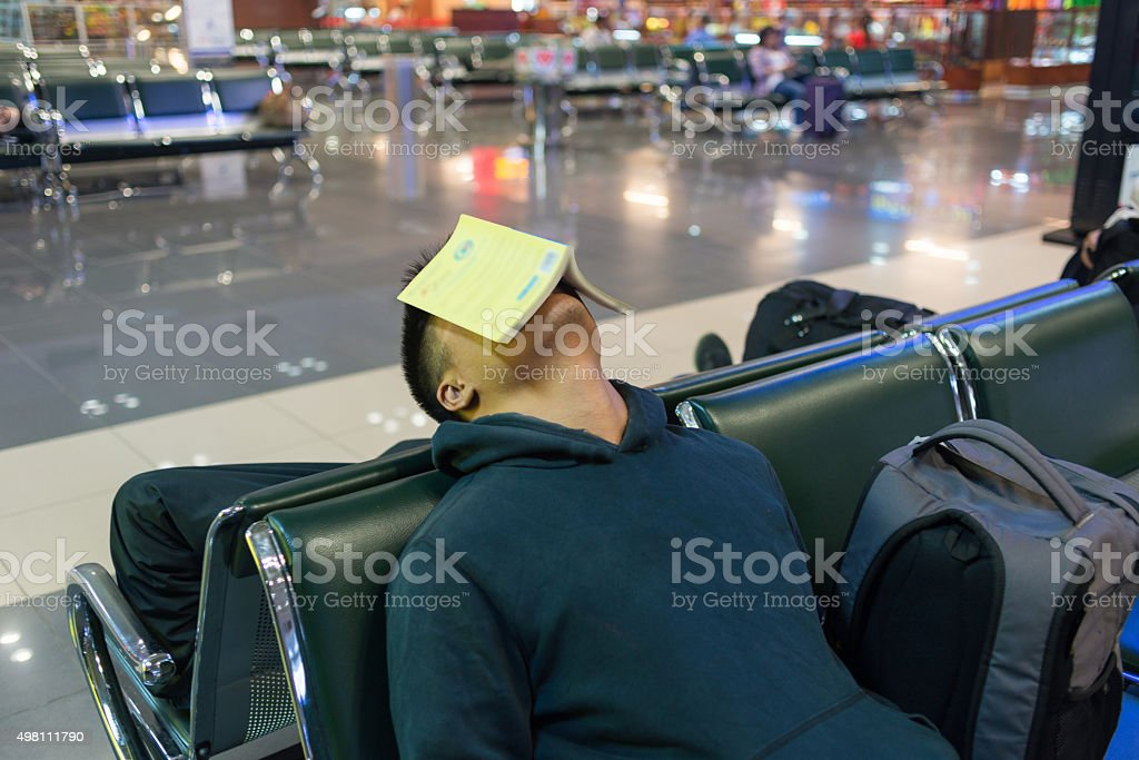 Fall asleep while reading a book in waiting lounge stock photo