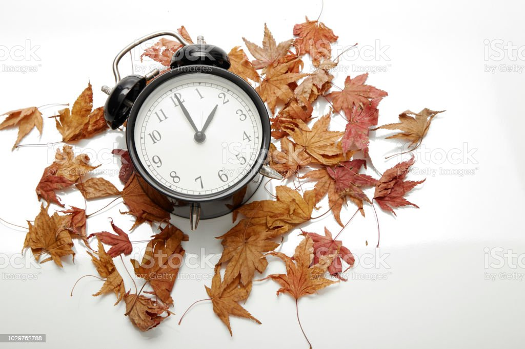 Image of autumn Time Change, Fall back concept, Dry leaves and...