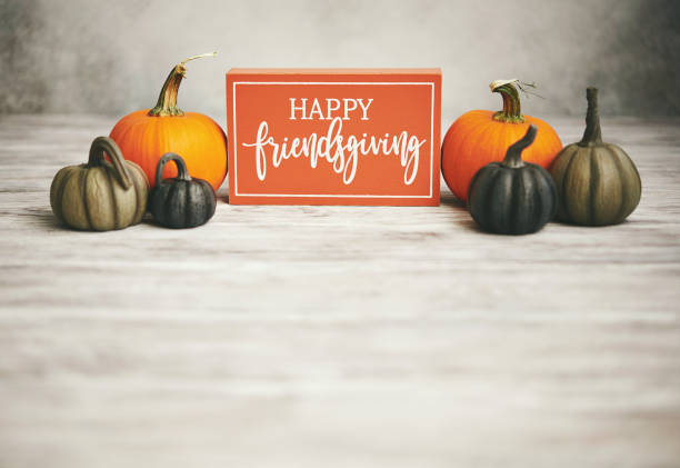 Fall background with pumpkins and Happy Friendsgiving Sign stock photo