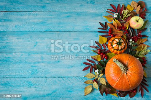istock Fall border of apples, berries, pumpkins on blue table, copy space 1058743642