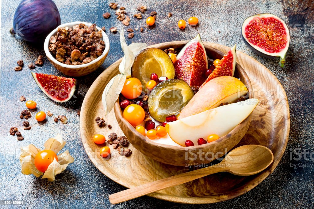 Fall breakfast bowl with chocolate granola, coconut yogurt and autumn seasonal fruits and berries. Healthy vegan, vegetarian breakfast table stock photo