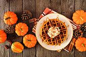 ホイップトッピング、キャラメル、ピーカンと秋の朝食カボチャスパイスワッフル。ダークウッドに対するトップビューテーブルシーン。
