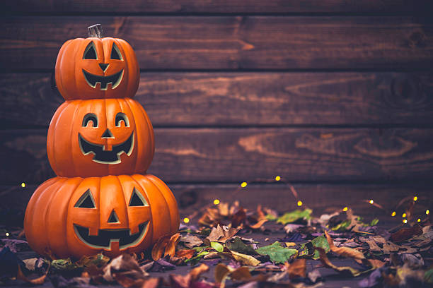 Fall celebrations. Halloween Jack O Lanterns with leaves stock photo