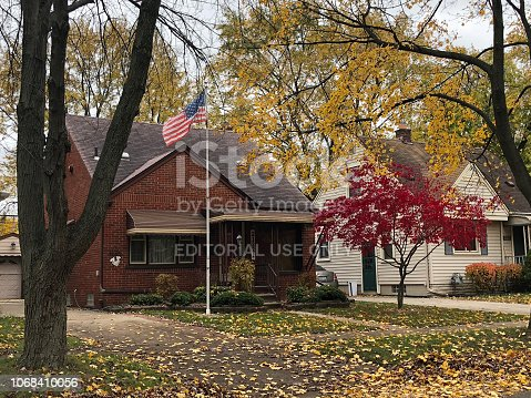Dearborn, Michigan-November 8, 2018:  Typical 1950's suburban home in the autumn with colored leaves on the tree and covering the grass.  An American flag waves in the breeze.
