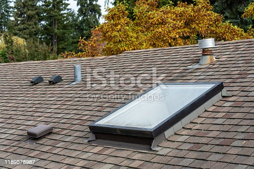 Rooftop view of residential asphalt shingle roof, skylight, roof vents, fall foliage in background
