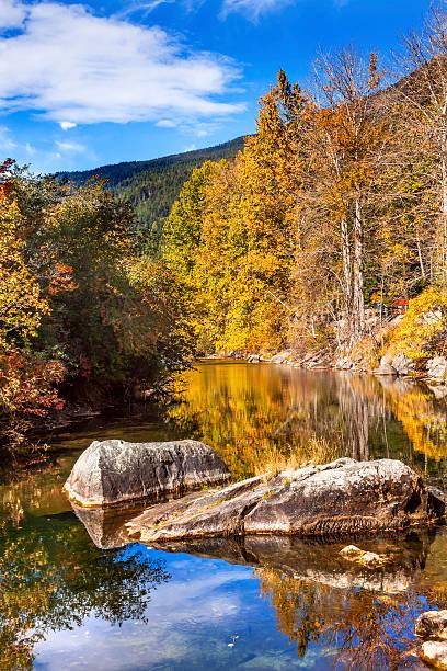 fall colors orange fire reflection wenatchee river washington - leavenworth washington stock photos and pictures