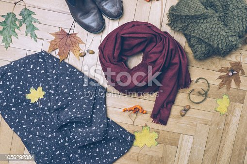 840310962istockphoto Fall female outfit. Ð¡ool-weather clothes concept: boots, dress, sweater, scarf and autumn decorations. Background with yellow leaves and autumn rowan. Top view. 1056292384