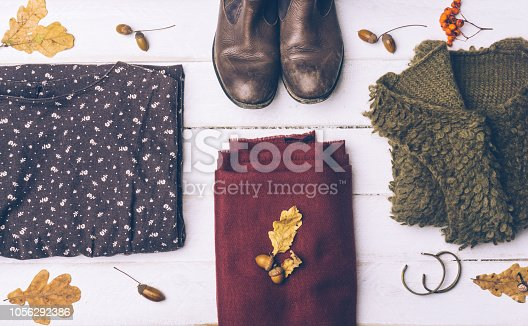 840310962istockphoto Fall female outfit. Ð¡ool-weather clothes concept: boots, dress, sweater, scarf and autumn decorations. Background with yellow leaves and autumn rowan. Top view. 1056292386