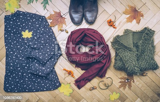 840310962istockphoto Fall female outfit. Ð¡ool-weather clothes concept: boots, dress, sweater, scarf and autumn decorations. Background with yellow leaves and autumn rowan. Top view. 1056292400