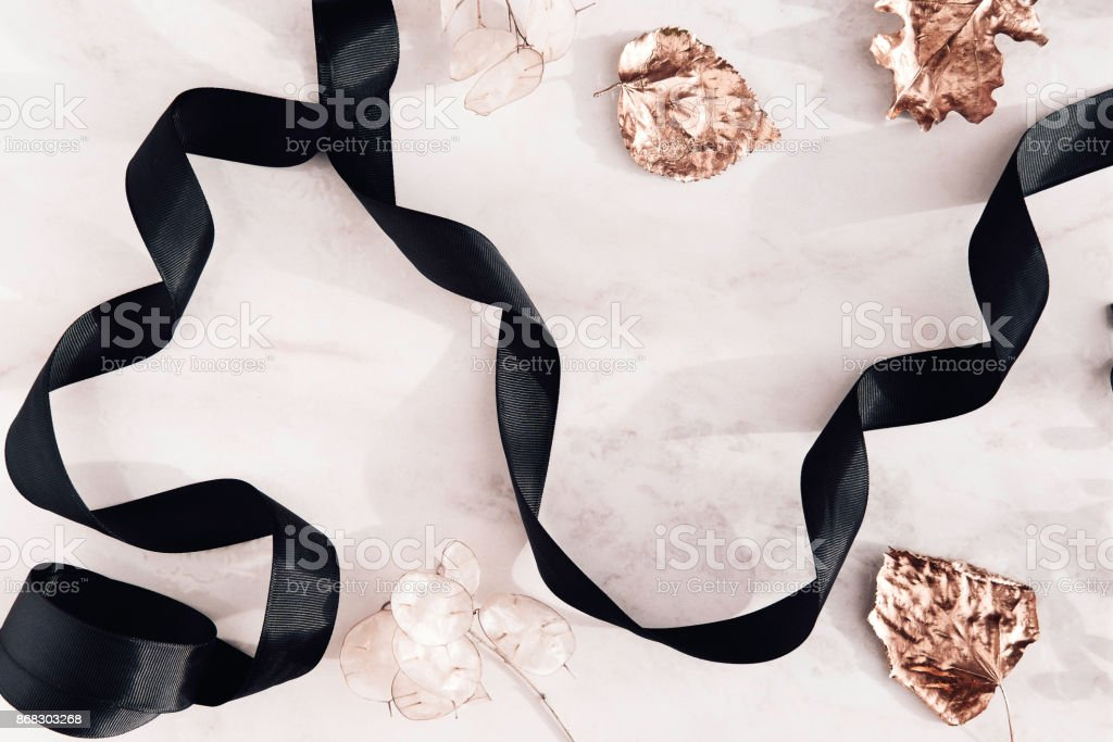 Fall flatlay with black ribbon and gold leaves stock photo
