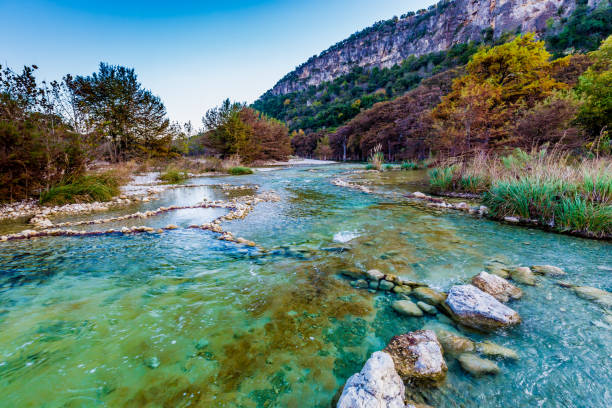 Fall foliage on the crystal clear Frio River in Texas. Fall Foliage on Trees Lining the Crystal Clear Frio River at Garner State Park, Texas, with Mount Old Baldy in Background. mount baldy stock pictures, royalty-free photos & images