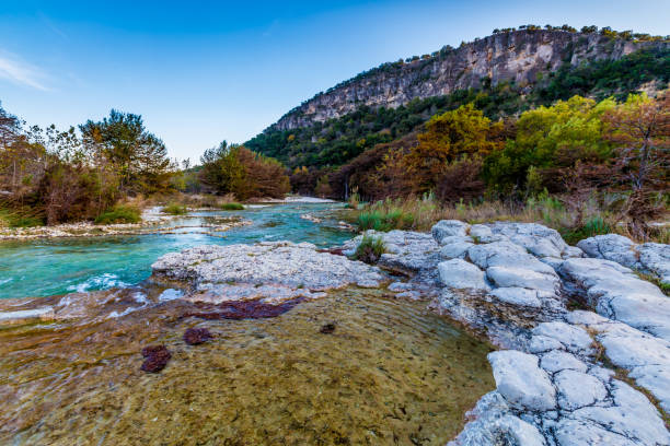 Fall foliage on the crystal clear Frio River in Texas. Old Mount Baldy with Fall Foliage on Trees Lining the Crystal Clear Frio River at Garner State Park, Texas. mount baldy stock pictures, royalty-free photos & images