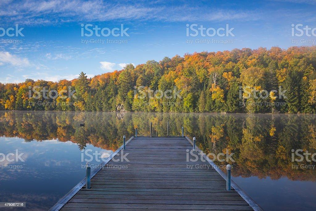 Fall foliage reflecting on a calm lake stock photo