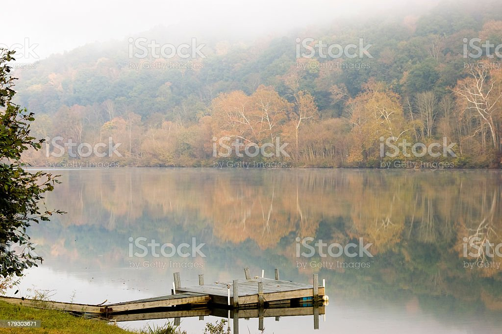 Fall foliage reflections on a misty morning stock photo