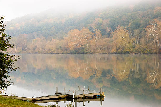 Fall foliage reflections on a misty morning Reflections of fall foliage on the river on a misty morning. Mist is causing a painterly effect in the trees. Focus on ramp. monongahela river stock pictures, royalty-free photos & images