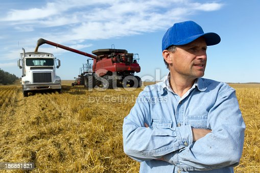 A royalty free image from the agrictultural industry of a farmer in front of two pieces of farm equipment during harvest.