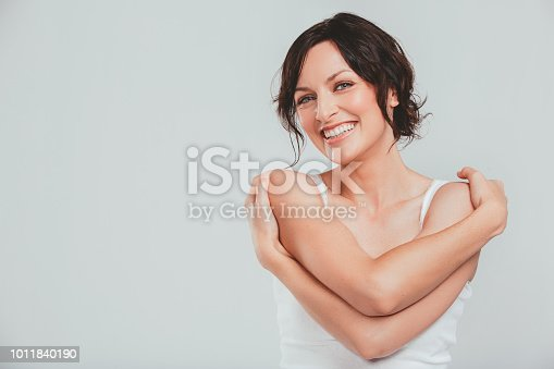 Studio shot of an attractive woman hugging herself against a gray background