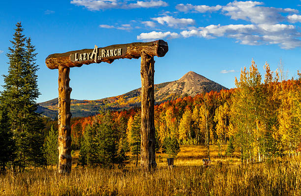 Fall in Steamboat Springs Colorado Colorado Lazy Ass Ranch entrance at sunset on warm fall evening with Hahn Peak in distance and changing yellow Aspen trees on mountain slopes steamboat springs stock pictures, royalty-free photos & images
