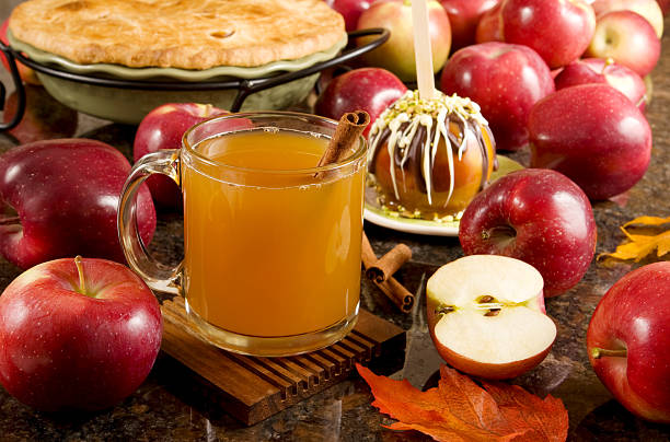 Fall is here Delicious hot, spiced apple cider  A cup of hot apple cider, caramel apple and apple pie surrounded by fresh fruits hot apple cider stock pictures, royalty-free photos & images