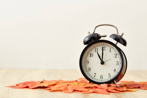 Cтоковое фото fall leaves and black and white alarm clock with copy-space