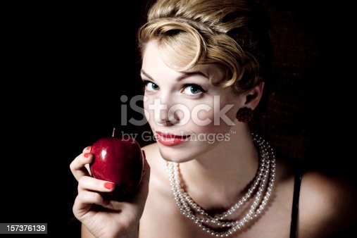 Beautiful blonde woman holding the red apple. 50s Style Portrait, Fall of Man, Temptation Concept.