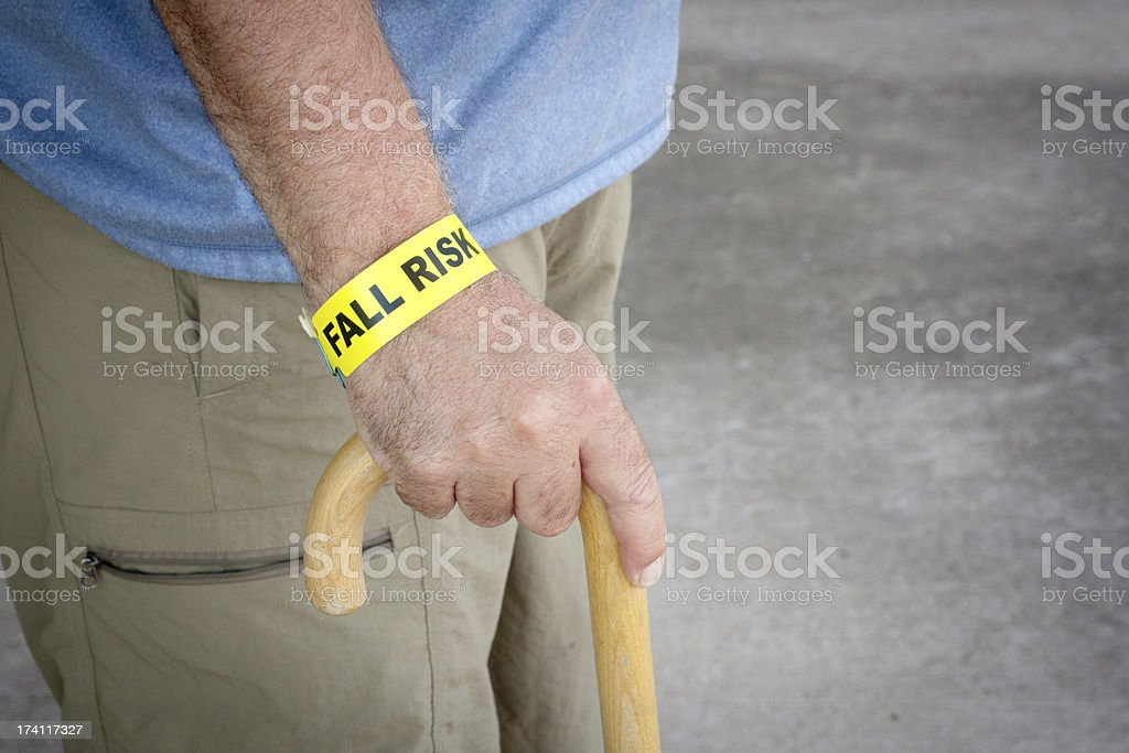 Fall Risk Bracelet And Wooden Cane royalty-free stock photo