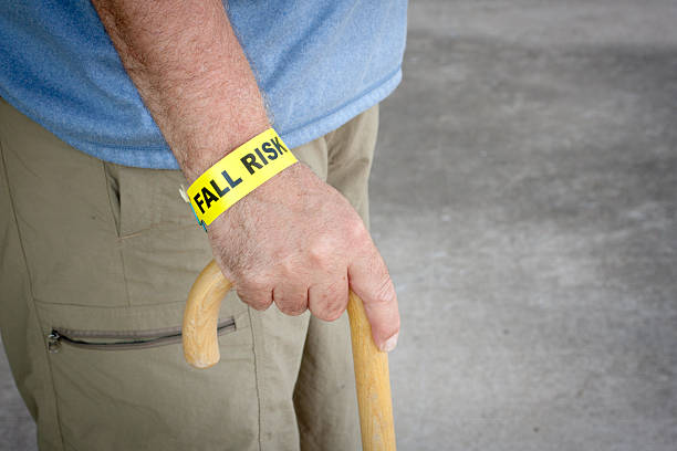 fall risk bracelet and wooden cane - inpatient stock pictures, royalty-free photos & images