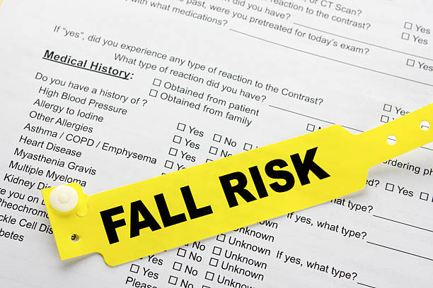 Fall Risk With Hospital  Paperwork A yellow fall risk patient bracelet on top of a hospital questionnaire paperwork wristband stock pictures, royalty-free photos & images