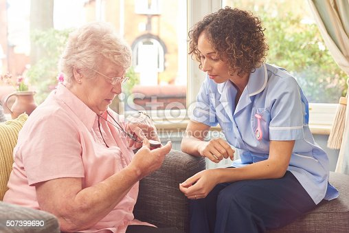 a care nurse demonstrates to a senior woman how her panic pendant would work in the event of a fall or medical emergency.