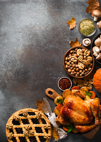 Fall thanksgiving table with roasting chicken or turkey, nuts, pie, pumkins and other food on dark background, rustic, top view, vertical