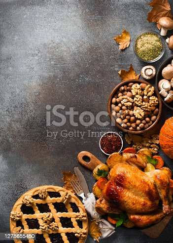 istock Fall thanksgiving table with roasting chicken or turkey, nuts, pie, pumkins and other food on dark background 1278655450