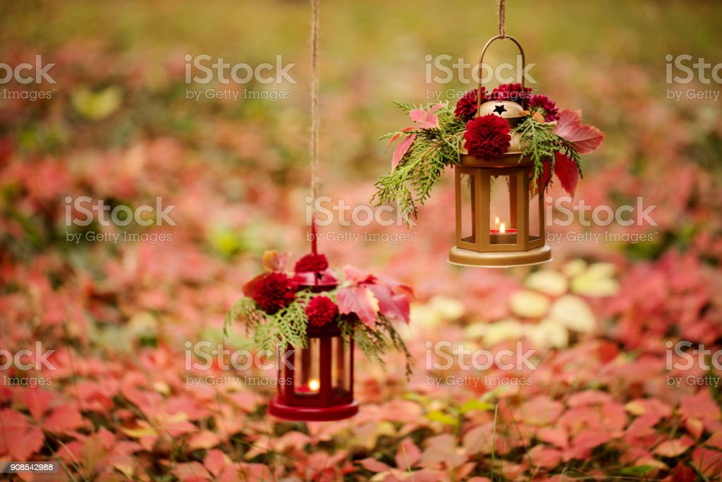 Fall time. Autumn decoration. Candlesticks in the form of lanterns with daisy decor, juniper and autumn red leaves. stock photo