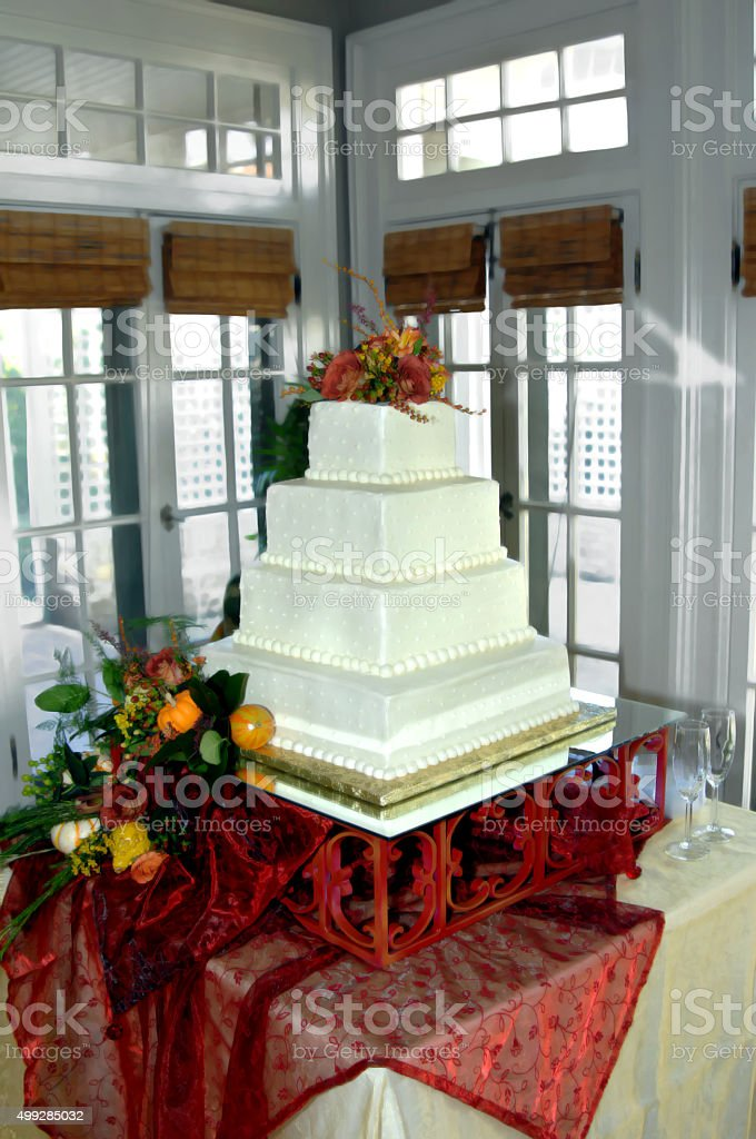 Square tiered, wedding cake, sits atop a beatuiful metal cake stand....