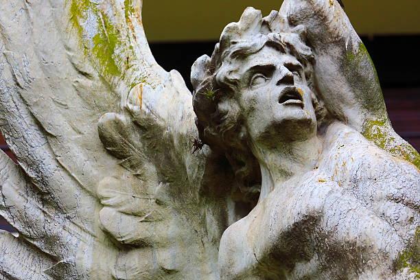 fallen angel looking to skies, black background, recoleta cemetery - brüllender tod stock-fotos und bilder
