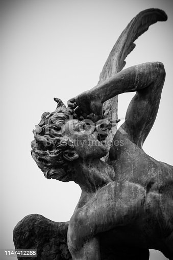 Fallen Angel sculpture on a cloudy day at Park El Retiro Madrid