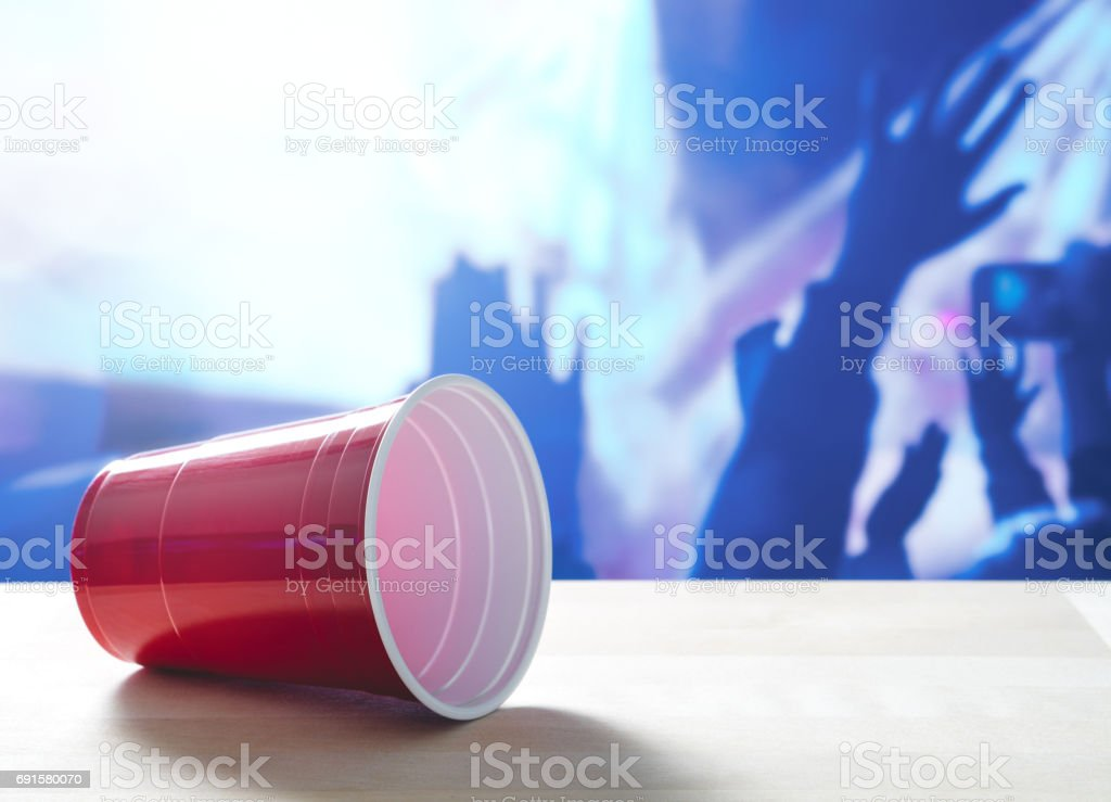Fallen plastic red party cup on its side on a table. Nightclub or disco full of people dancing on the dance floor in the background. Perfect for marketing and promotion for events or college fest. stock photo