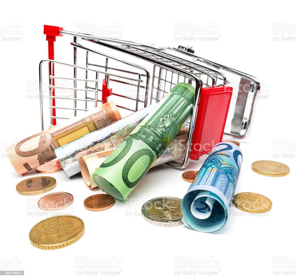 Fallen shopping cart with money inside stock photo