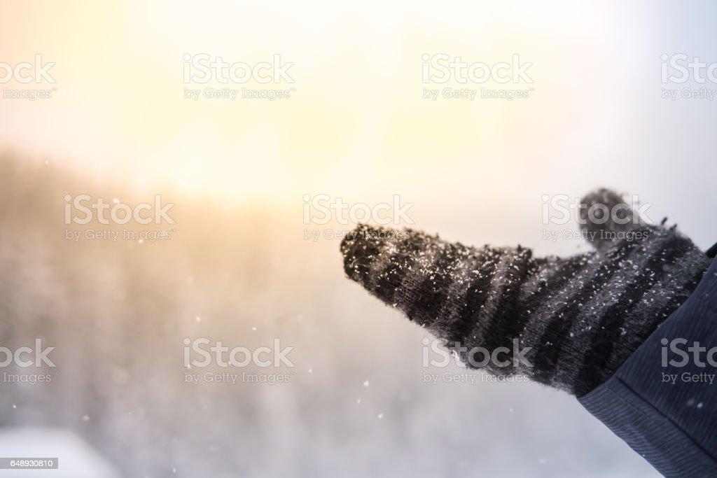 Fallen snow on woman's hand wearing globe stock photo