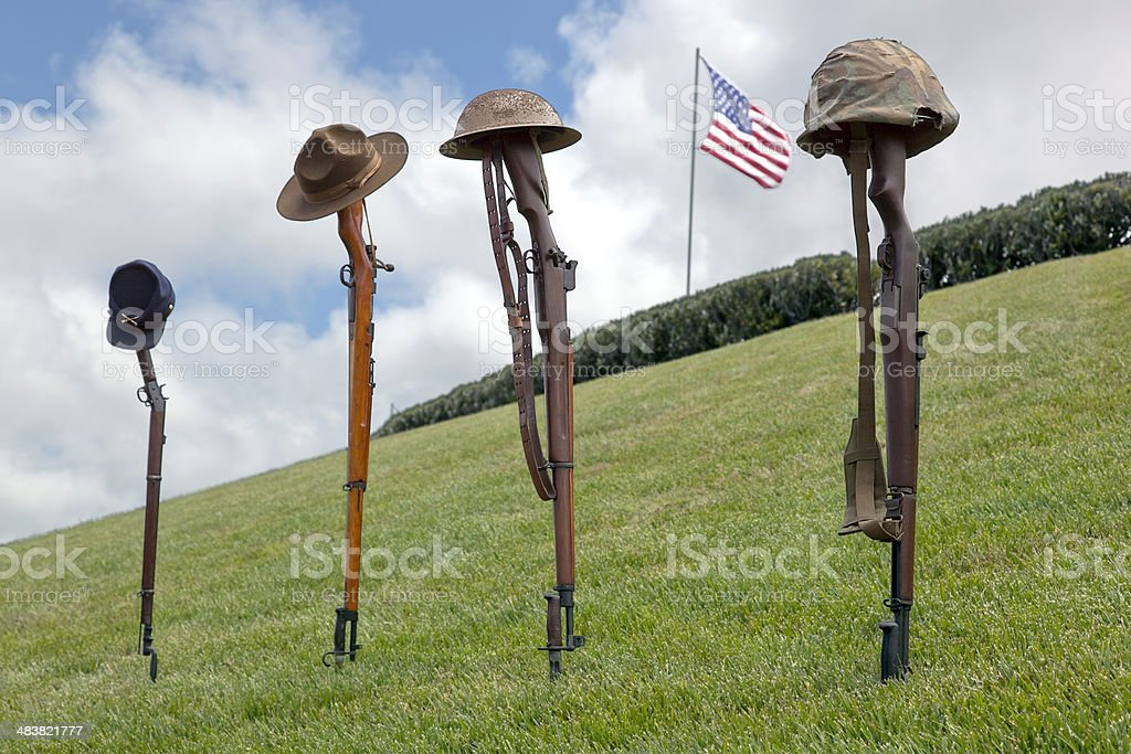 Fallen Soldier Battle Crosses Vintage, antique rifles and soldier's hats and helmets forming Fallen Soldier Battle Crosses, American Flag behind, left to right, from eras of Civil War, Spanish American War, WWI, WWII. American Flag Stock Photo