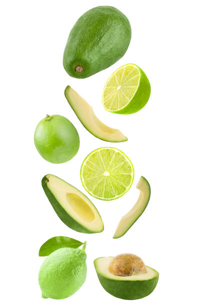 Falling avocado and lime isolated on white background stock photo