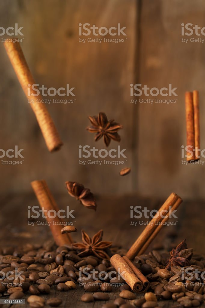 Falling cinnamon and star anise on old black marble table. stock photo