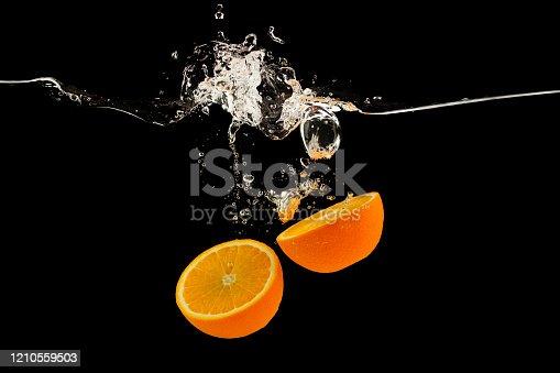 1169153675 istock photo Falling citrus fruits. Orange halves splattering into water on black background 1210559503