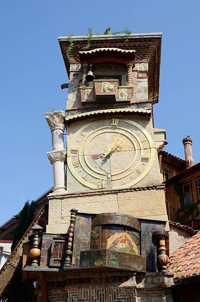 falling clock tower in sololaki old district of tbilisi,georgia. - klokkentoren met luidende klokken stockfoto's en -beelden
