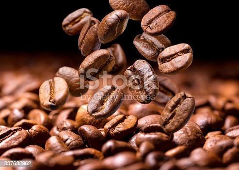 istock Falling coffee beans. Dark background with copy space, close-up 837682962