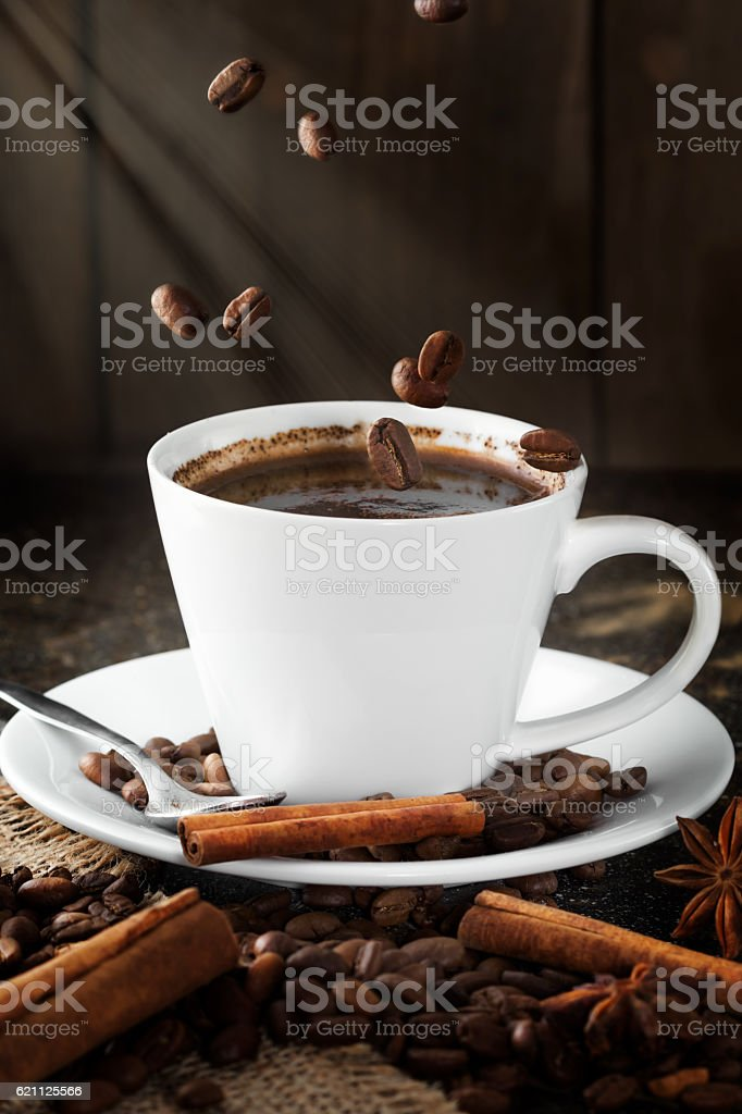 Falling coffee beans in a cup with coffee. stock photo