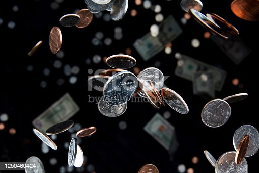 Studio shot of falling coins that appear to defy gravity in the air represent the economy and finance with a nickel in focus