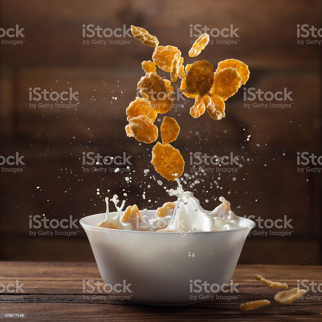 Falling corn flakes with milk splash on wood stock photo