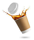 falling disposable paper cup with coffee splash isolated on white background