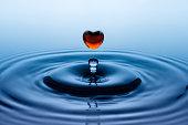 Falling down drop of red liquid in heart shape